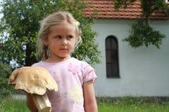 拿着蘑菇的小女孩 免版税库存照片