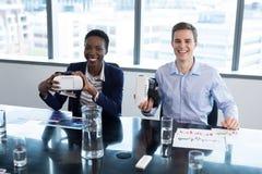 拿着虚拟现实耳机的微笑的董事画象  免版税库存图片