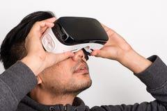 拿着虚拟现实风镜的年轻亚裔人半档案  免版税图库摄影