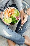 拿着虾有海草的,鲕梨,黄瓜,萝卜,芝麻的牛仔裤的女孩捅碗 库存照片