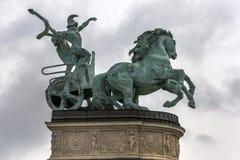拿着蛇的一个人的雕象驾驶他用马拉的运输车战争的标志在英雄` s正方形的在布达佩斯在匈牙利 库存照片