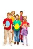 拿着蛋形状五颜六色的卡片的愉快的孩子 免版税库存照片