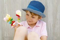 拿着蛋白软糖的愉快的小孩男孩在手中串起 用不同的unhelthy五颜六色的甜点的孩子 免版税库存图片