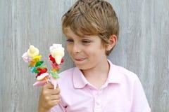 拿着蛋白软糖的愉快的小孩男孩在手中串起 用不同的unhelthy五颜六色的甜点的孩子 库存照片