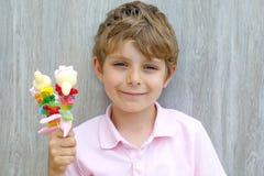 拿着蛋白软糖的愉快的小孩男孩在手中串起 用不同的unhelthy五颜六色的甜点的孩子 库存图片