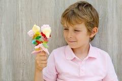 拿着蛋白软糖的愉快的小孩男孩在手中串起 用不同的unhelthy五颜六色的甜点的孩子 免版税库存照片