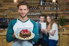 拿着蛋糕和顾客的板材侍者画象在背景中 免版税库存照片