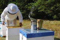 拿着蜂箱和火轮的蜂农 库存图片