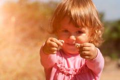 拿着蜗牛的好奇小女孩 图库摄影