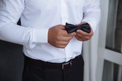 拿着蝶形领结的人 典雅的绅士clother 库存照片
