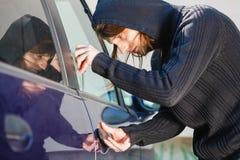 拿着螺丝刀的Thieft人闯进汽车 库存照片