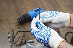 拿着螺丝,蓝色电skrewdriver,在木地板上的钻子的人 室内修理的概念 图库摄影