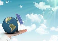 拿着行星地球和太阳电池板的手的数字式综合图象反对天空 库存图片