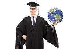 拿着行星地球的年轻毕业生 免版税图库摄影