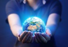 拿着行星-世界地球日概念的手 库存照片
