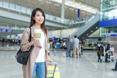 拿着行李和咖啡在香港国际性组织airp的妇女 免版税库存图片