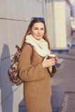 拿着袋子和杯子热的茶或咖啡的美丽的深色的妇女,站立在街道 库存图片
