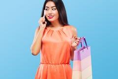 拿着袋子和电话在蓝色背景的购物的愉快的亚裔妇女黑星期五假日 复制空间为 免版税图库摄影