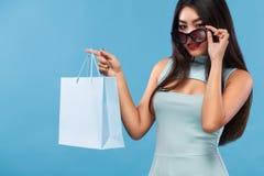 拿着袋子和电话的购物的愉快的亚裔妇女隔绝在蓝色背景黑星期五假日 复制空间为 免版税库存照片
