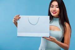 拿着袋子和电话的购物的愉快的亚裔妇女隔绝在蓝色背景黑星期五假日 复制空间为 库存照片