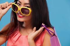 拿着袋子和电话的购物的愉快的亚裔妇女隔绝在蓝色背景黑星期五假日 复制空间为 库存图片