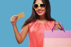 拿着袋子和电话的购物的愉快的亚裔妇女隔绝在蓝色背景黑星期五假日 复制空间为 图库摄影