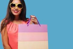 拿着袋子和电话的购物的愉快的亚裔妇女隔绝在蓝色背景黑星期五假日 复制空间为 免版税库存图片