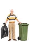 拿着袋子垃圾的老人 免版税库存图片