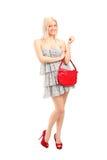 拿着袋子的一个可爱的性感的白肤金发的女性 免版税库存图片