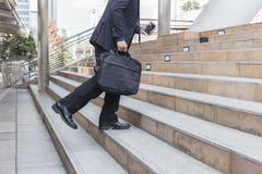 拿着袋子的商人,当走向上在台阶室外在城市时 免版税库存照片