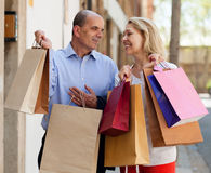 拿着袋子的愉快的恋人家庭在购物以后 库存图片