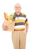拿着袋子的成熟人有很多杂货 免版税库存照片