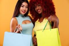 拿着袋子的购物的愉快的美国黑人和亚裔妇女被隔绝在橙色背景黑星期五假日 免版税库存图片