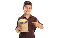 拿着袋子芯片的快乐的男孩 免版税库存照片