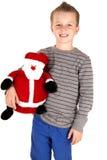 拿着被充塞的圣诞老人的年轻男孩愉快地微笑 库存照片