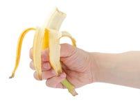 拿着被吃的香蕉的手。 免版税库存图片