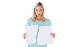 拿着被撕毁的纸片的严肃的妇女 免版税库存照片