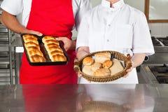 拿着被烘烤的面包的厨师在厨房里 库存图片