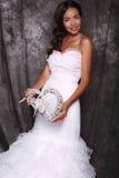 拿着装饰心脏的婚礼礼服的美丽的新娘 图库摄影