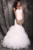 拿着装饰心脏的婚礼礼服的美丽的新娘 库存图片