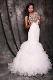 拿着装饰心脏的婚礼礼服的美丽的新娘 免版税图库摄影