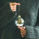 拿着装饰玻璃球,方形的庄稼的灰色毛线衣的妇女 免版税图库摄影