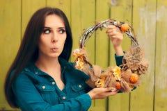拿着装饰秋天花圈的惊奇的女孩 库存图片