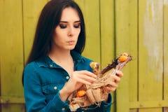 拿着装饰秋天花圈的想法的女孩 免版税库存照片