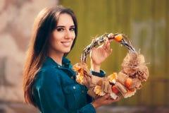 拿着装饰秋天花圈的愉快的女孩 库存照片