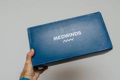 拿着西班牙豪华Medwinds箱子纸板的人 免版税库存照片