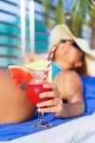 拿着西瓜新鲜的汁圆滑的人饮料鸡尾酒的妇女帽子 免版税库存图片