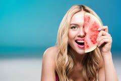 拿着西瓜的微笑的白种人妇女在面孔前面片 免版税库存照片