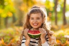 拿着西瓜的愉快的女孩坐叶子 库存图片