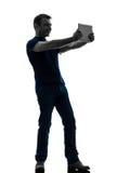 拿着观看的数字式片剂剪影的人 库存图片